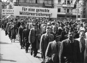 Labour Day parade, march with a banner: 'For a Fair Military Insurance!' Schweizerisches Sozialarchiv, Sozarch_F_5047-Fb-090.