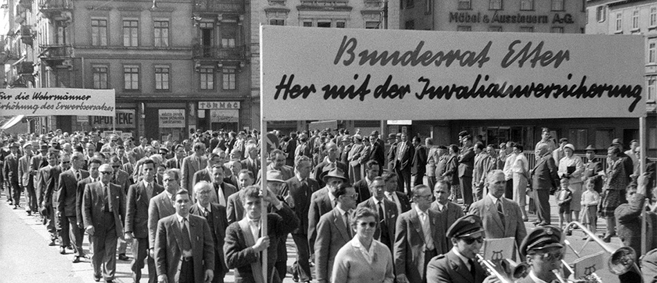 Labour Day Parade: March of musicians under the banner 'Federal Councillor Etter: We Demand Disability Insurance', 1957, source: Sozialarchiv, Zurich.